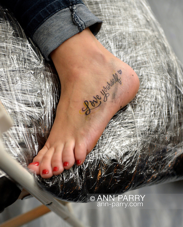 On her foot, a woman has just gotten a new tattoo of 'Love yourself' in black script, at the United Ink Flight 914 tattoo convention at the Cradle of Aviation museum of Long Island.