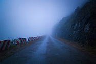 Empty road of Ma Pi Leng pass disappears into the mist, between Dong Van and Meo Vac, Ha Giang Province, Vietnam, Southeast Asia