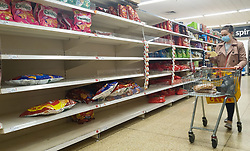 © Licensed to London News Pictures. 27/10/2021. London, UK. A shopper walks past nearly empty shelves of Walkers crisp in Sainsbury's, north London, as food shortages continue, following Brexit. According to the British Retail Consortium, three in five retailers expect prices to increase in the run up to Christmas, and the ongoing labour shortages are making the situation worse. Photo credit: Dinendra Haria/LNP