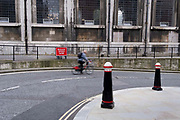 A passing cyclist is blurred as he moves past a reduce speed now sign, round a bend of a side street in the City of London, the capitals financial district, on 1st September 2021, in London, England.