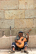 A blind musician plays guitar in Oaxaca, Mexico.