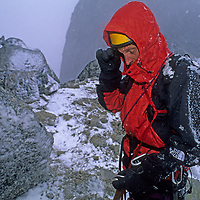 MOUNTAINEERING, Bugaboo Mts., B.C., Canada. Roger Schley (MR) in storm, retreating from ascent of Pigeon Spire.