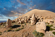 Statue heads at sunset, from froint, of an eagle, Herakles & Apollo, & Zeus (left), in front of the stone pyramid  62 BC Royal Tomb of King Antiochus I Theos of Commagene, west Terrace, Mount Nemrut or Nemrud Dagi summit, near Adıyaman, Turkey .<br /> <br /> If you prefer to buy from our ALAMY PHOTO LIBRARY  Collection visit : https://www.alamy.com/portfolio/paul-williams-funkystock/nemrutdagiancientstatues-turkey.html<br /> <br /> Visit our CLASSICAL WORLD HISTORIC SITES PHOTO COLLECTIONS for more photos to download or buy as wall art prints https://funkystock.photoshelter.com/gallery-collection/Classical-Era-Historic-Sites-Archaeological-Sites-Pictures-Images/C0000g4bSGiDL9rw