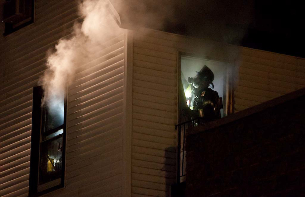 Somerville, MA 02/06/2012.A firefighter overhauls a burning room on the second floor of a house on Jacques St. that caught fire on Monday evening..Wicked Local Photo by Alex Jones