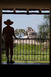 Mexico, Yucatan, Chichen Itza, woman gazing at view of Mayan ruins of El Caracol (the Observatory) from Mayaland Hotel, PR,