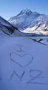 I Love NZ is carved in the snow above Hooker Lake, with Aoraki in the background; Aoraki/Mt. Cook National Park, New Zealand