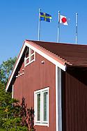 Svenska och japanska flaggan vid ett falurött hus i Sweden Hills, Japan