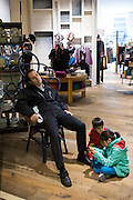 An exhausted father sleeps in a store as his children play at his feet in Chicago, IL.