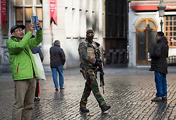 "© Licensed to London News Pictures. 23/11/2015. Brussels, Belgium. A Belgian soldier patrolling past tourists in The Grand Place, the main square in central Brussels   where the city is currently on ""lockdown"" amid ""imminent threat"" of Paris-style bomb and gun attacks. Photo credit: Ben Cawthra/LNP"