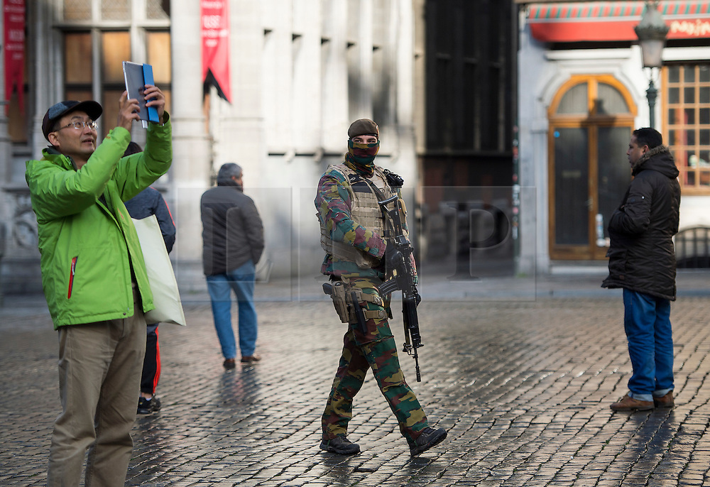 """© Licensed to London News Pictures. 23/11/2015. Brussels, Belgium. A Belgian soldier patrolling past tourists in The Grand Place, the main square in central Brussels   where the city is currently on """"lockdown"""" amid """"imminent threat"""" of Paris-style bomb and gun attacks. Photo credit: Ben Cawthra/LNP"""