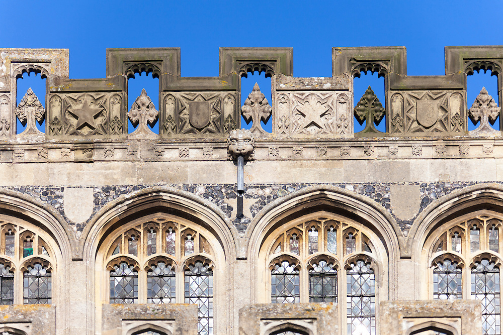 Perpendicular 15th century windows and castellated parapet with open work at Saint Peter and Saint Paul church, Lavenham, Suffolk, UK