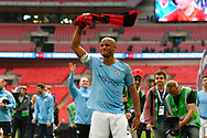 Vincent Kompany (4) of Manchester City swings a red and black scalf above his head as he celebrates winning the FA Cup during the The FA Cup Final match between Manchester City and Watford at Wembley Stadium, London, England on 18 May 2019.