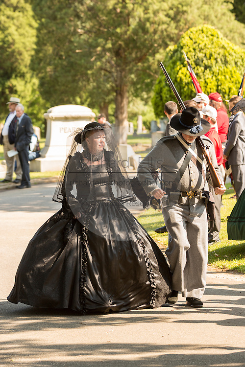 A Civil war re-enactor in period mourning costume is escorted by a soldier during a service at Elmwood Cemetery to mark Confederate Memorial Day May 2, 2015 in Columbia, SC. Confederate Memorial Day is a official state holiday in South Carolina and honors those that served during the Civil War.