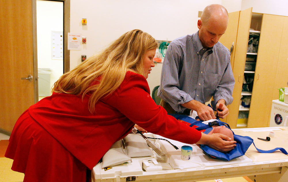 Michael Grabinski, two weeks old is removed from an inflatable jacket after coming out of an MRI machine at The Children's Hospital by his mother Calee (L) and Dr. David Brumbaugh in Aurora, Colorado August 23, 2010 during a research study on obesity in infants.  The overall theme of the study is to understand the continuum of growth that starts really at conception, and to understand if the earliest phases of growth impacts later risk for obesity.  REUTERS/Rick Wilking (UNITED STATES)