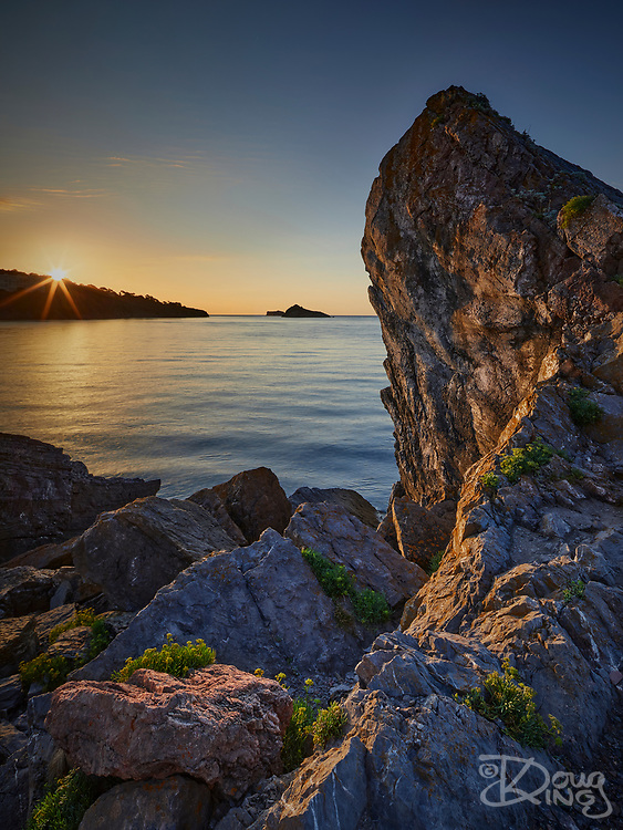 An English Riviera sunrise illuminates a rock outcrop at Meadfoot in Torbay.