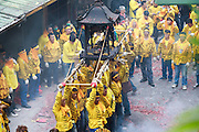 Holding a Gods palanquin aloft and offering it toward a temple during a Chinese religious festival.