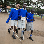 Three boys, blind and visually impaired, at the Kalimani Primary School, a regular school which they attend. The paper is a poem typed in Braille which they are going to read out at local college at an event with other blind children.The Kenya Society for the Blind is a long standing charity which works to make blind people able to function in the community as a whole.