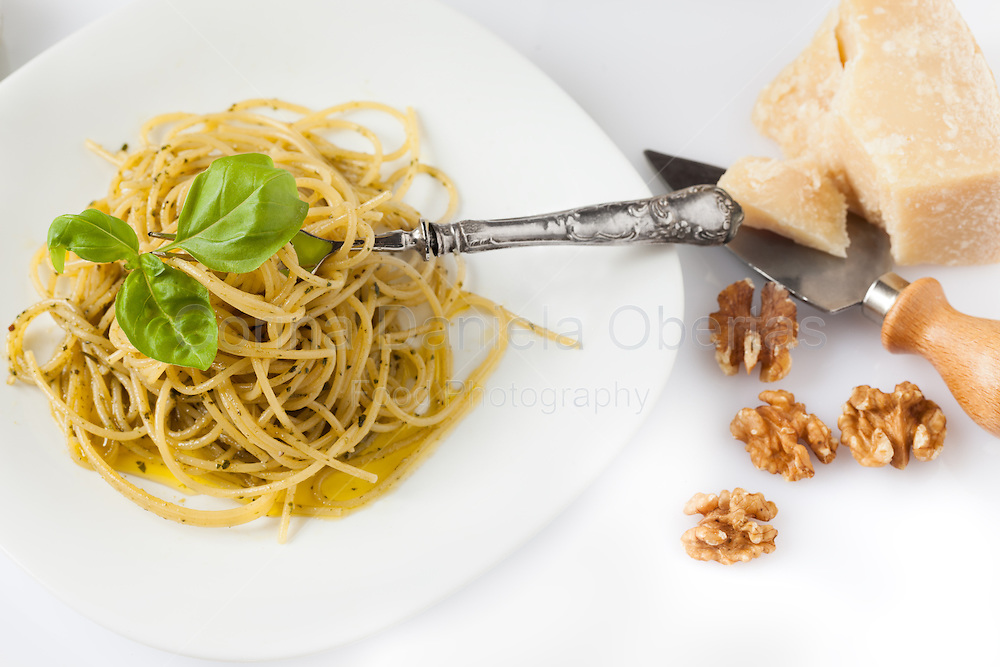 Plate of spaghetti with pesto together with parmesan and nuts, over white background.