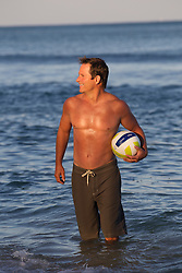 shirtless middle aged man holding a volleyball in the ocean