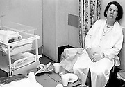 On a labour ward at Kings College Hospital, London, a young mother sits back and rests before being transferred to a bed on the maternity ward. Wearing a hospital gown and an identity wrist tag, leans back exhausted on a wall with eyes closed, reflecting on the last 24 hours of labour, contractions and the birth of her first child, a baby girl who    sleeps in a cot next to her mother. Tissues and a drink cups are on the table in front but the new mum is too tired to reach out for a sip. This is from a documentary series of pictures about the first year of the photographer's first child Ella. Accompanied by personal reflections and references from various nursery rhymes, this work describes his wife Lynda's journey from expectant to actual motherhood and for Ella - from new-born to one year-old.