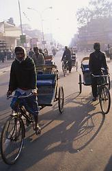 Men riding cycle rickshaws waiting for custom in Indian street,