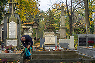A man cleans a gravestone in Rakowicki cemetery in Krakow, Poland 2019.