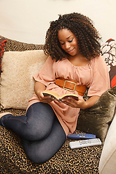 Young black woman relaxing reading.