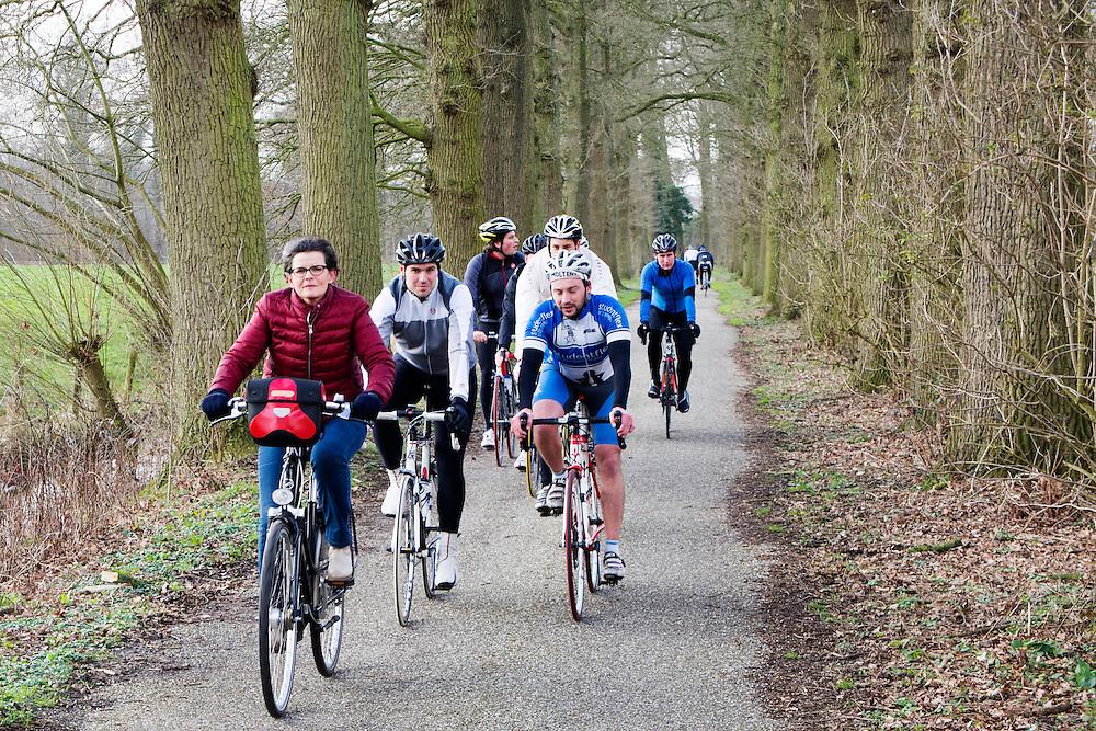 Een groep wielrenners wil een fietsende vrouw inhalen bij het landgoed Rhijnauwen. Het gedrag van groepen racefietsers levert nog geregeld problemen in het verkeer, sommige fietsers gedragen zich lomp. Het landgoed Rhijnauwen is een buurtschap bij Bunnik. Op het landgoed ligt ook het Fort Rhijnauwen, het grootste fort van de Nieuwe Hollandse Waterlinie.<br /> <br /> A group of cyclists want to overtake a woman on a bike at the estate Rhijnauwen. The estate Rhijnauwen is a hamlet in Bunnik with the Fort Rhijnauwen, the largest fortress of the New Dutch Waterline.