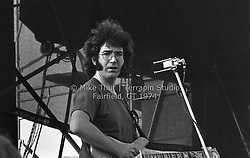 Jerry Garcia looking at the photographer and playing Guitar with The Grateful Dead at Dillon Stadium in Hartford CT on 31 July 1974. Close in sidelong shot. Wall of Sound behind Jerry. Photo by Michael Thut, Fairfield CT.