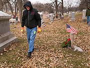 14 DECEMBER 2019 - DES MOINES, IOWA: A volunteer walks through Woodland Cemetery after placing a Christmas wreath on a veteran's grave. Volunteers working with Wreaths Across America placed Christmas wreaths on the headstones of more than 600 US military veterans in Woodland Cemetery in Des Moines. The cemetery, one of the first in Des Moines, has the graves of veterans going back to the War of 1812.    PHOTO BY JACK KURTZ