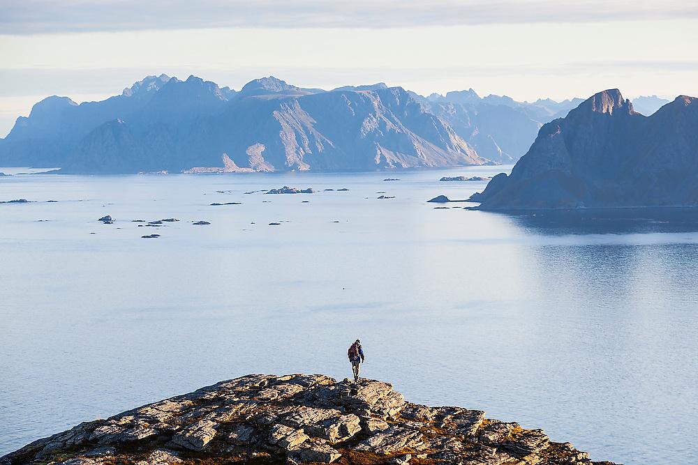 Parmenter Welty looks out towards Mosken (right) and Moskenesoya Islands from Vaeroy Island, Lofoten Islands, Norway.