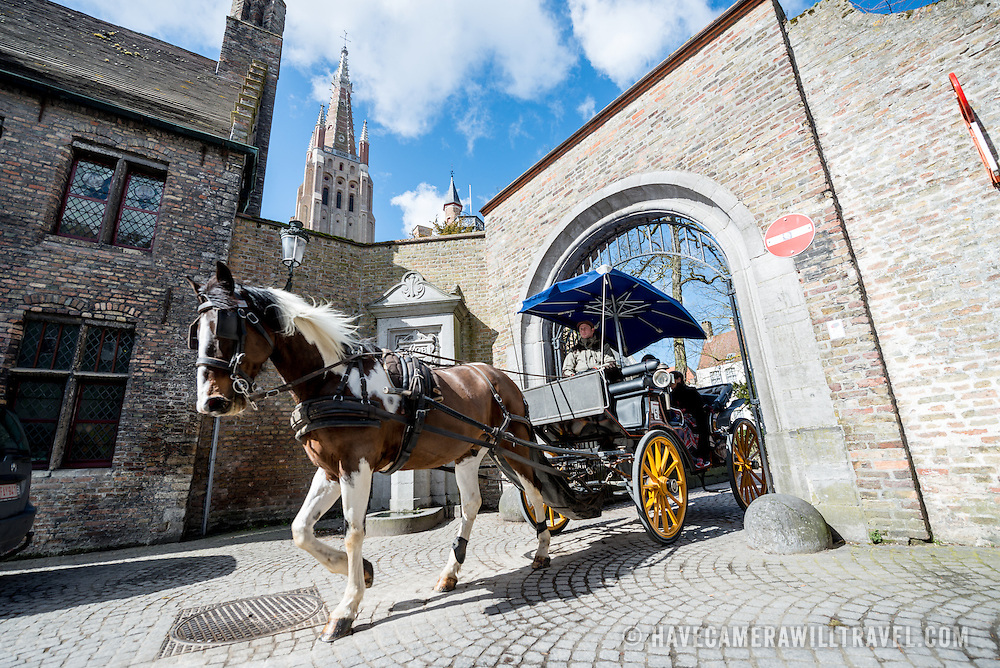 Tourists tour the cobblestone streets of the historic center of Bruges in a horse drawn carriage.