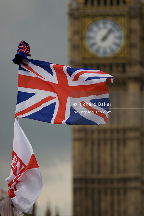 Britain's Union Jack flag flies in a breeze with British Parliament's Big Ben clock tower at the Palace of Westminster in the background. As a symbol of parliamentary power and a national democracy, the colours flutter in a breeze alongside the Thames River on the southern Lambeth bank side. The clock shows just after 1 in the afternoon. The Palace, also known as the Houses of Parliament or Westminster Palace, is where the two Houses of the Parliament of the United Kingdom (the House of Lords and the House of Commons) conduct their business. It is therefore a potent symbol for British Governmental power, influence and a world-famous landmark for tourists. Big Ben is the name of the clock's bell and not the tower itself.