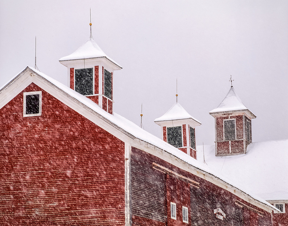 Detail of red barn with three cupolas, during winter snowstorm, Underhill, VT