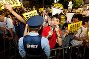 A young man breaks the cordon and challenges police at a protest against the revision of article 9 of the Japanese Constitution outside the Prime-Minister's house in Kasumigasaki, Tokyo, Japan. Monday June 30th 2014. Over 10,000 people showed their support for Japan's unique peace constitution and called on the government to halt its reinterpretation of Article 9 allowing Collect Self Defence which is expected to become law on July 1st