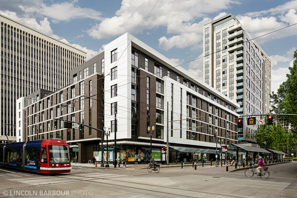 An apartment building dominates the scene as people pass by on bikes, walking, and also a light rail moves through.