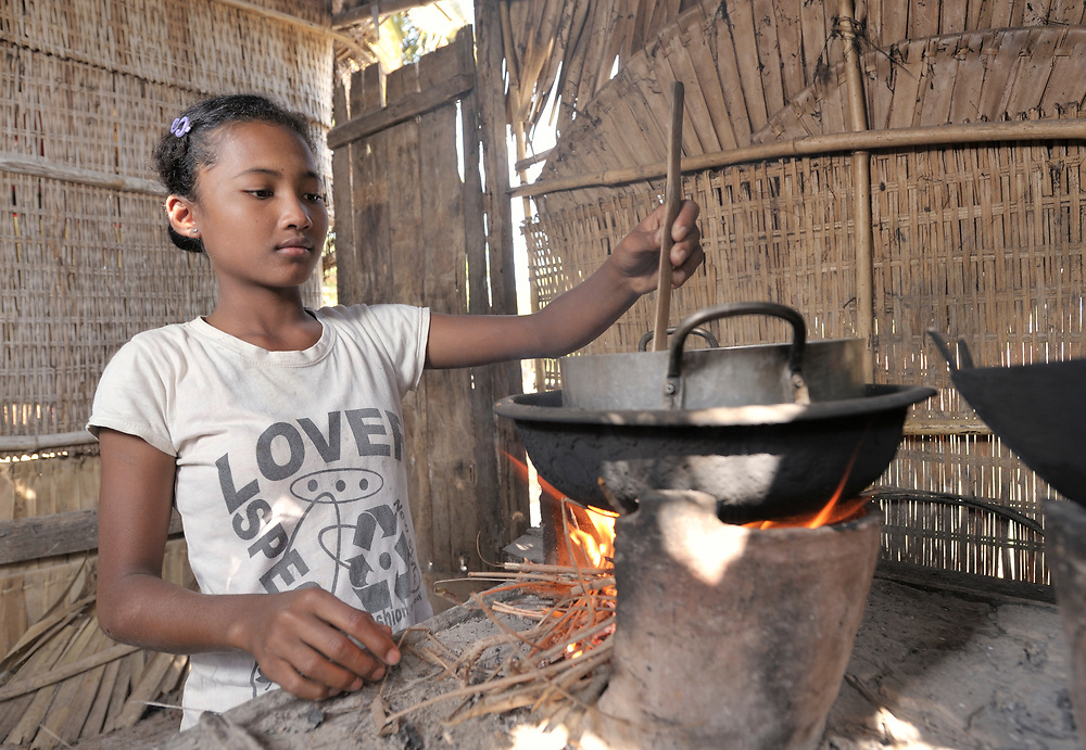 Srey Mao, 14, cooks a meal in Khnach, a village in the Kampot region of Cambodia. Along with another sister, she lives with and takes care of her aging grandmother. Her parents died of AIDS.