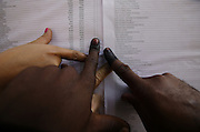 Angolans look for their names on a list, before voting at a polling station in Luanda, today 31 August