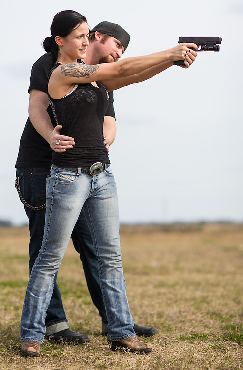 Woman with a handgun getting a shooting lesson.
