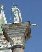 The Piazzetta di San Marco is  an open space connecting the south side of the Piazza to the waterway of the lagoon. The Piazzetta lies between the Doge's Palace on the east and Jacopo Sansovino's Libreria which holds the Biblioteca Marciana on the west. Column topped by a statue of Saint Theodore, who was the patron of the city before St Mark, holding a spear and with a crocodile to represent the dragon which he was said to have slain.