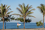 A surfer walks to Ipanema beach for early morning surf in Rio de Janeiro, Brazil.