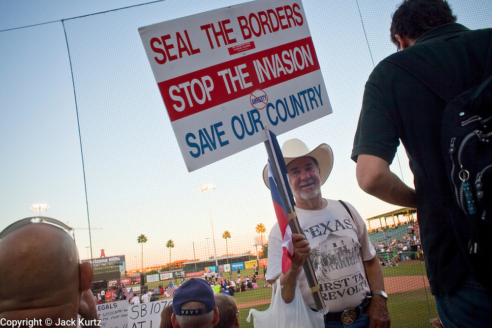 """May 29 - TEMPE, AZ: A man from Texas shows support for Arizona's SB1070 in Tempe, AZ, Saturday. About 3,000 people attended a """"Buy Cott Arizona"""" rally at Tempe Diablo Stadium in Tempe, AZ Saturday night. The rally was organized by members of the Arizona Tea Party movement to show support for Arizona law SB1070. SB1070 makes it an Arizona state crime to be in the US illegally and requires that immigrants carry papers with them at all times and present to law enforcement when asked to. Critics of the law say it will lead to racial profiling, harassment of Hispanics and usurps the federal role in immigration enforcement. Supporters of the law say it merely brings Arizona law into line with existing federal laws.  Photo by Jack Kurtz"""