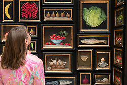 © Licensed to London News Pictures. 20/06/2018. LONDON, UK. A visitor views food inspired paintings on the Geoffrey Stead stand at The Art & Antiques Fair Olympia which runs 20 to 27 June at Kensington Olympia.  Photo credit: Stephen Chung/LNP