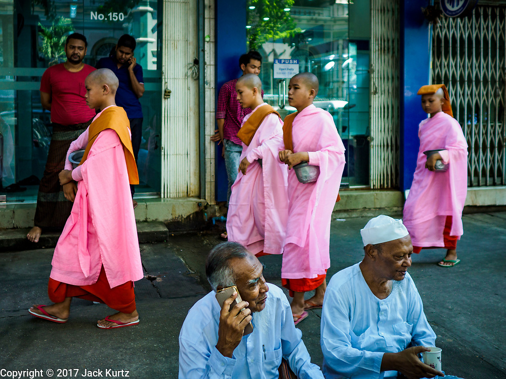 """24 NOVEMBER 2017 - YANGON, MYANMAR: Buddhist nuns, also known as """"Bhikkhuni"""" pass Muslim men sitting on a Yangon sidewalk. Many Muslims in overwhelmingly Buddhist Myanmar feel their religion is threatened by a series of laws that target non-Buddhists. Under the so called """"Race and Religion Protection Laws,"""" people aren't allowed to convert from Buddhism to another religion without permission from authorities, Buddhist women aren't allowed to marry non-Buddhist men without permission from the community and polygamy is outlawed. Pope Francis is to arrive in Myanmar next week and is expected to address the persecution of the Rohingya, a Muslim ethnic minority in western Myanmar. Some Muslims and Christians are concerned that if the Pope's comments take too strong of pro-Rohingya stance, he could exacerbate religious tensions in the country.  PHOTO BY JACK KURTZ"""