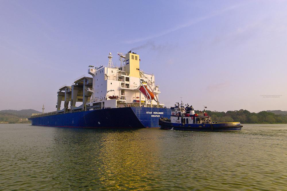 A container ship and tugboat transit the Panama Canal (Gatun Lake), Panama