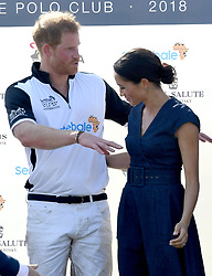 Meghan, Duchess of Sussex, wearing a navy blue dress by Carolina Herrera, and Prince Harry, Duke of Sussex stand together following the Sentebale ISPS Handa Polo at the Royal County of Berkshire Polo Club on July 26, 2018.