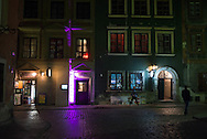 People walk past local pubs and shops in Warsaw, Poland