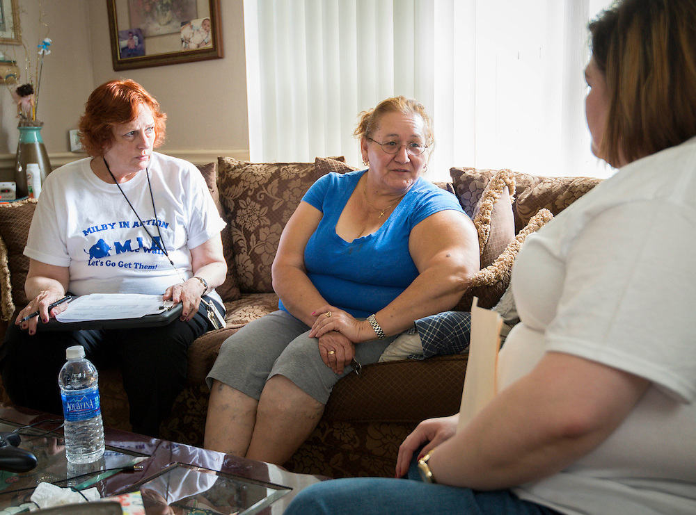 """Mary Smith and Heidi Cisneros talk with Berta Borrego about her son's grades during the """"Milby in Action"""" home visit initiative to reach students with excessive absences or failing grades at Milby High School, October 14, 2013."""