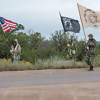 Pete Tsinnijinnie, US flag, Larry Ashkie, POW, and Jerry C. Lee, Navajo Nation, walk together along AZ-264, during the veterans walk to the Navajo Nation Council Chambers in Window Rock on Wednesday.