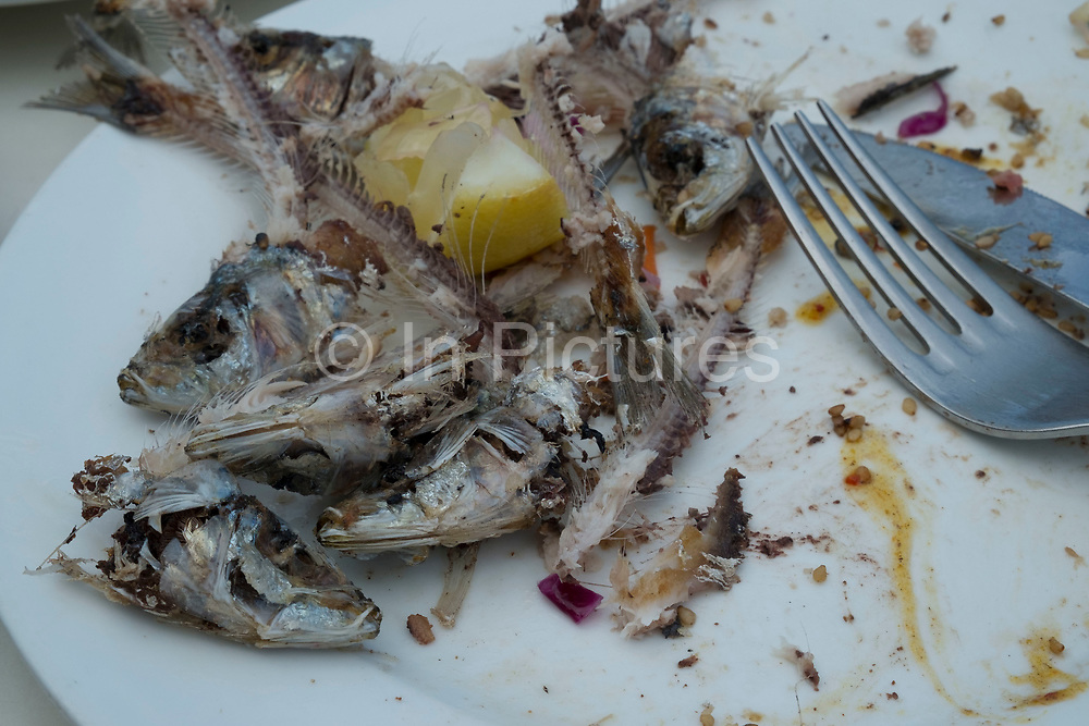 A finished plate of sardine bones on a dinner plate with knife and fork in La Palma, Canary Islands, Spain. La Palma, also San Miguel de La Palma, is the most north-westerly Canary Island in Spain. La Palma has an area of 706km2 making it the fifth largest of the seven main Canary Islands.